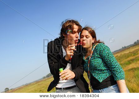 Concept: stay young! Young couple in their twenties blowing soap bubbles together in heath landscape with blue sky background