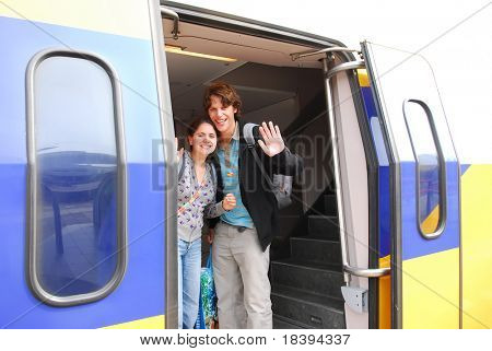 Young couple in their twenties smiling and waving goodbye from a departing train in holland