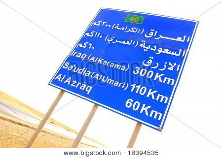 Road sign with direction to Iraq on desert road in Jordan