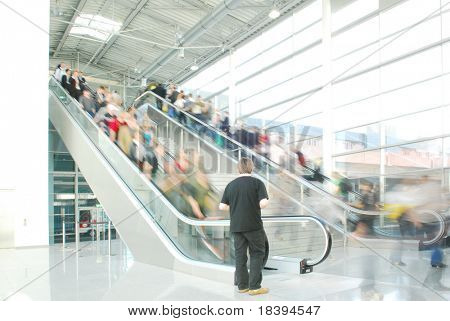 People rushing on escalator in business center, mall or airport to work with motion blur