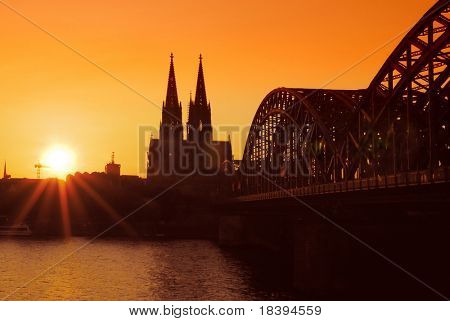 Sunset in Cologne with view on the 'dom' cathedral and the 'hohenzollern' railway bridge over river rhine