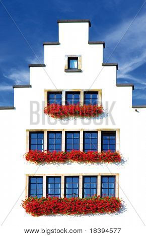 Facade of historic white house in Cologne with red geraniums for the windows and blue sky background