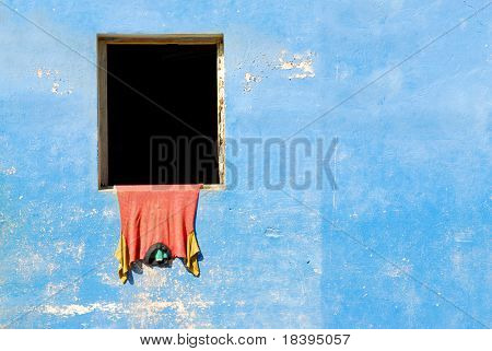 Blue vintage wall with red t-shirt hanging out of window in colonial town Baracoa on Cuba