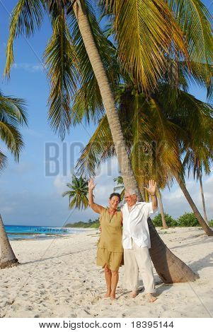 Happy senior couple on the beach greeting with their hands, enjoying retirement on tropical destination: Maria la Gorda on caribbean island Cuba