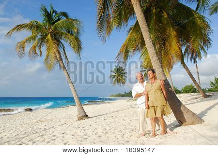 Happy senior couple embracing each-other and enjoying retirement on tropical destination: Maria la Gorda beach on caribbean island Cuba