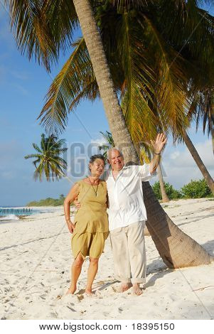 Happy senior couple embracing each-other and man greeting with his hand, enjoying retirement on tropical destination: Maria la Gorda beach on caribbean island Cuba