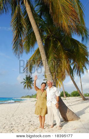 Happy senior couple, embracing eachother and woman greeting with her hand, enjoying retirement on tropical destination: Maria la Gorda beach on caribbean island Cuba
