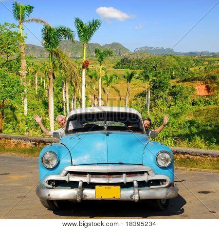 European senior couple having fun touring around Vinales valley, Cuba, in an vintage old-timer car