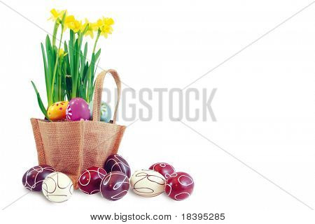Easter basket filled with chocolate easter eggs and yellow daffodil flowers