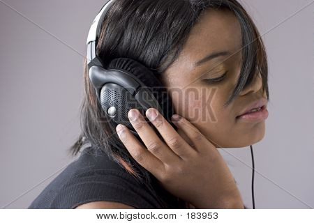Attractive Young Black Woman Listening To Music On Headphones