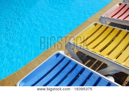 blue background with sun reflected in the swimming-pool water and colorful sunbathing chairs