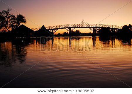 Romantic sunrise in Zapata swamp area with silhouette of bamboo bridge on caribbean island Cuba