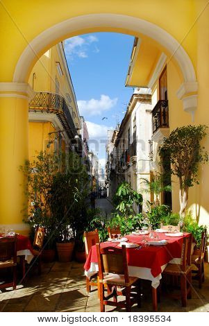Traditional restaurant exterior with table settings on the terrace and view on old havana at caribbean island Cuba