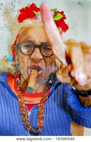 HAVANA â?? CIRCA DECEMBER 2008: An eccentric old Cuban lady smokes cigar and points finger circa December 2008 in Havana, Cuba.