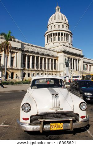 HAVANA - CIRCA DEC 2008 : Capitolio building with vintage white old american car circa December 2008 in Havana, Cuba. The Capitolio building is an exact copy of the Capitol in Washington.