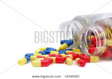 Two pots of yellow, blue and red capsule pills isolated on white background