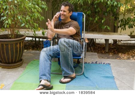 Handsome Man Seated In Blue Chair On Phone Waving