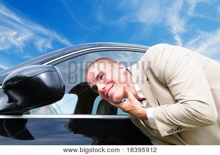 Vain business man checking his looks in the mirror of his car, with blue sky background