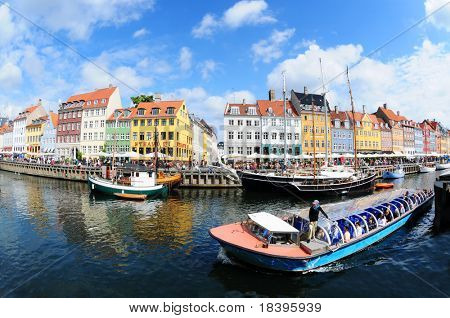 COPENHAGEN - AUGUST 12: Fish eye view of colorful houses and tour boat in famous canal Nyhavn August 12, 2009 in Copenhagen, Denmark.