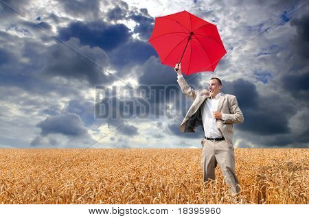 Businessman with red umbrella jumping in a field of wheat with dark cloud background