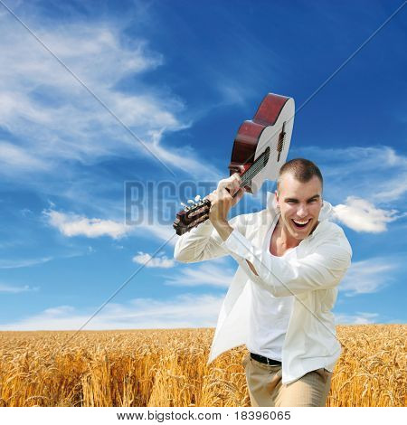 Enthusiastic man smashing with his guitar outdoors in the field with blue sky square background