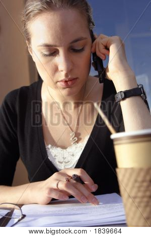 Young Woman Doing Paperwork At Cafe