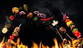 Collage of grilled meat skewers and vegetables on black background poster