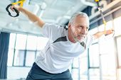 Senior Sportsman Training With Resistance Band In Sports Center poster
