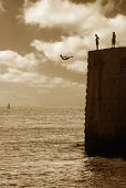 Teenagers jumping from the wall of ancient fortress in to Mediterranean Sea in Acre, Israel (sepia t