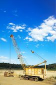 stock photo of oversize load  - yellow big excavator with empty cabin staying on the clay - JPG