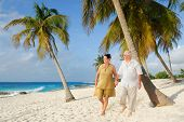 Active senior couple walking on the beach, enjoying retirement on tropical destination: Maria la Gor