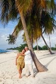 Romantic senior couple on the beach embracing each-other, enjoying retirement on tropical destination: Maria la Gorda on caribbean island Cuba poster