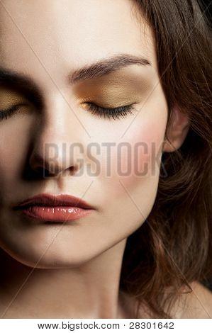 Retrato do close-up da bela jovem com olhos fechados com maquiagem elegante