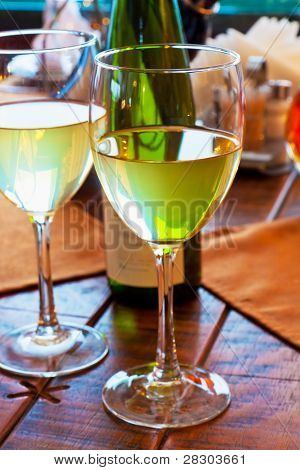 Two goblets with white wine on restaurant table