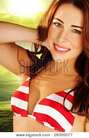 Beautiful smiling woman with auburn hair wearing a red and white striped bikini, outdoors against greenery