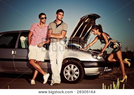 girl fixing car engine while couple of young man waiting by the car