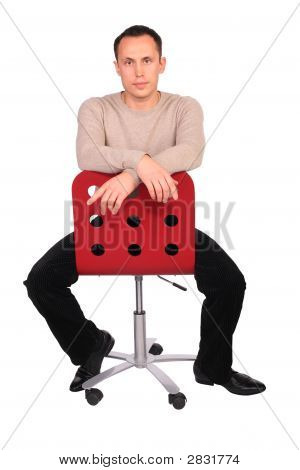 Young Man Sits On Red Chair