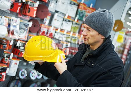 man during shopping choosing protective hard hat in hardware building supply store supermarket
