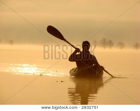 Man Kayaking On Lake At Dawn