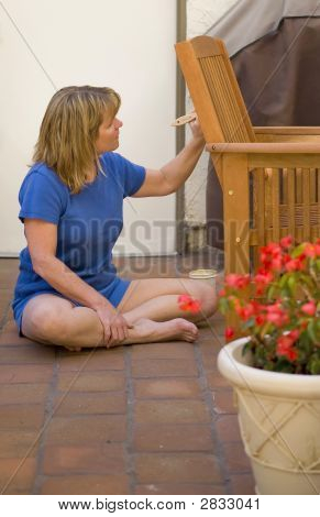 Woman Painting A Chair On The Patio