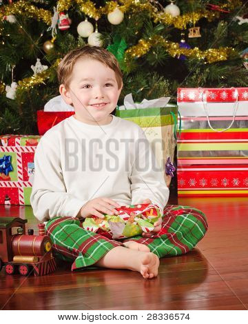 Young boy unwrapping presents on Christmas morning