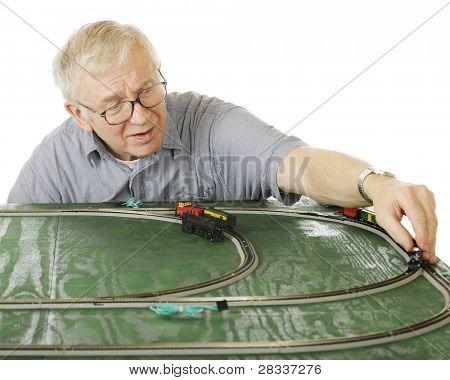 Um homem sênior, colocando um motor na pista, como ele define um novo conjunto de trem de N-calibram.  Foco é o