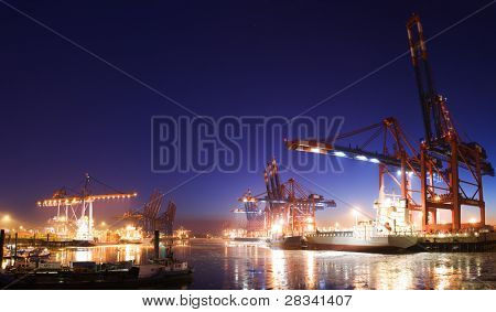 Panorama image of the illuminated cargo port in Hamburg at night with container terminals, cargo ships and cranes and a clear blue sky.