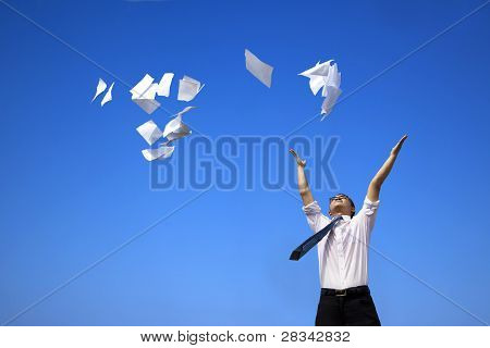 business man relaxing and throwing white papers to the blue sky