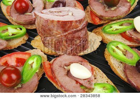 serpientes en plancha negra: Tartaletas con carne en rodajas, aislado sobre fondo blanco