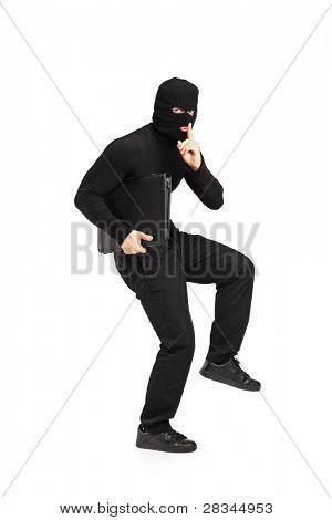Retrato de cuerpo entero de un hombre de la máscara de robo con un maletín con el dedo en los labios gesticular