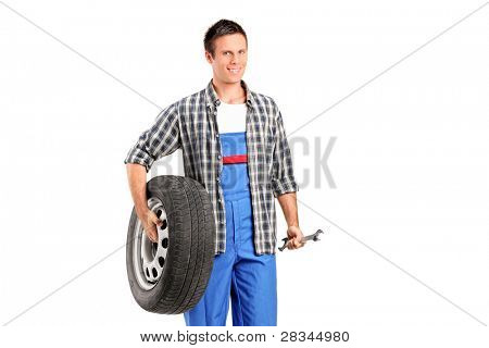 A mechanic holding a spare tire and a wrench isolated on white background