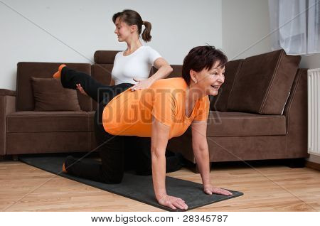 Coach Helping Senior Woman Exercising