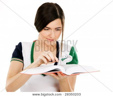 Young beautiful woman reading a book through magnifying glass, white background