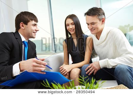 Portrait of modern couple listening to manager explanation of mortgage conditions
